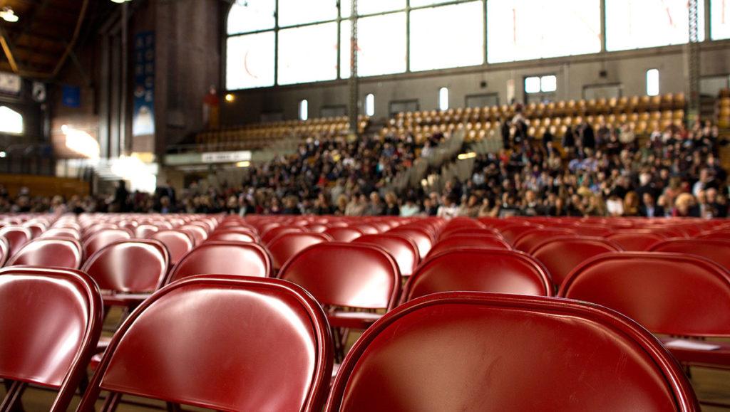 imagem ilustrativa: cadeiras de cinema vazias, com pública ao fundo em arquibancada