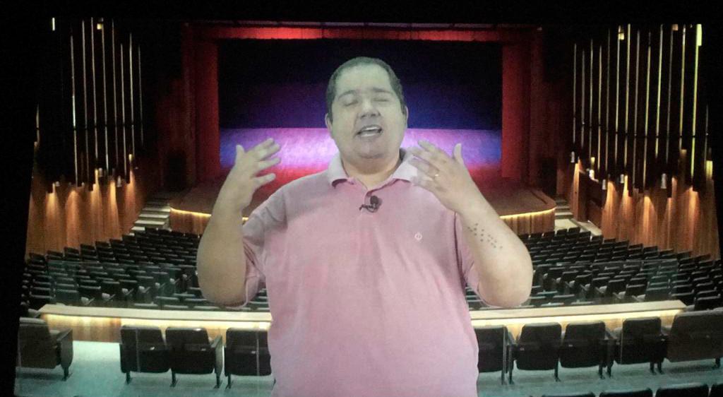 #ParaTodosVerem Imagem de uma videoaula do Curso de Introdução à Audiodescrição com professor Felipe Mianes, da cintura para cima, vestindo camisa rosa e gesticulando, à frente da fotografia de um grande teatro vazio..